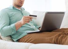 Chiuda su dell'uomo con il computer portatile e la carta di credito Fotografie Stock