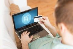 Chiuda su dell'uomo con il computer portatile e la carta di credito Immagini Stock Libere da Diritti