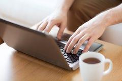 Chiuda su dell'uomo con il computer portatile e la tazza a casa Fotografia Stock Libera da Diritti