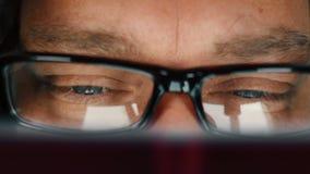 Chiuda su dell'uomo con il libro di lettura degli occhi azzurri ed occhiali di decollo per sfregare i suoi occhi video d archivio