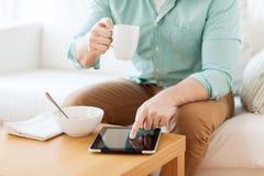 Chiuda su dell'uomo con il pc della compressa che mangia la prima colazione Immagine Stock