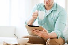 Chiuda su dell'uomo con il pc della compressa che mangia la prima colazione Immagini Stock Libere da Diritti