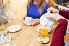 Chiuda su dell'uomo con il tè di versamento del vaso al caffè Immagini Stock Libere da Diritti