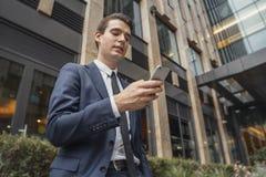 Chiuda su dell'uomo d'affari accanto al grattacielo che esamina lo schermo del telefono cellulare immagine stock libera da diritti