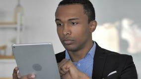 Chiuda su dell'uomo d'affari afroamericano casuale Browsing Internet sulla compressa stock footage