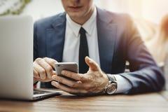 Chiuda su dell'uomo d'affari che esamina lo schermo del telefono cellulare il caffè della via fotografie stock