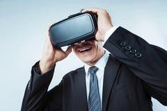 Chiuda su dell'uomo d'affari che indossa gli occhiali di protezione di realtà virtuale 3D Fotografia Stock