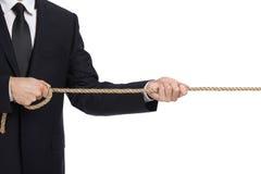 Chiuda su dell'uomo d'affari che tira la corda Immagini Stock Libere da Diritti