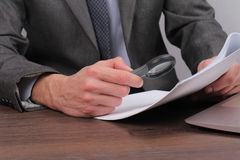 Chiuda su dell'uomo d'affari facendo uso della lente di ingrandimento per la lettura del contratto Lente d'ingrandimento e docume Immagine Stock Libera da Diritti