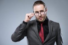 Chiuda su dell'uomo d'affari in vestito convenzionale che tocca i suoi vetri mentre stando, fotografia stock libera da diritti