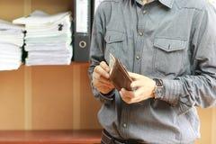 Chiuda su dell'uomo di affari che prende i soldi dei dollari dal portafoglio fotografie stock libere da diritti