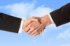 Chiuda su dell'uomo di affari che stringe le mani con la donna isolata sul fondo del cielo blu Immagini Stock