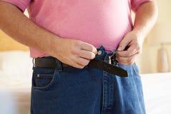 Chiuda su dell'uomo di peso eccessivo che prova a fissare i pantaloni Fotografie Stock Libere da Diritti