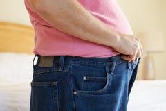 Chiuda su dell'uomo di peso eccessivo che prova a fissare i pantaloni Fotografia Stock Libera da Diritti