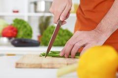 Chiuda su dell'uomo irriconoscibile che taglia la cipolla a pezzi verde Fotografia Stock