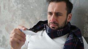 Chiuda su dell'uomo malato che controlla la temperatura video d archivio