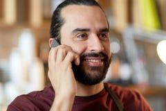 Chiuda su dell'uomo o del cameriere che rivolge allo smartphone Fotografia Stock Libera da Diritti
