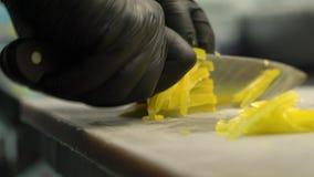 Chiuda su dell'uomo principale che produce ad insalata l'alimento sano e che taglia la carta a pezzi gialla sul tagliere nella cu video d archivio