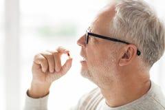 Chiuda su dell'uomo senior che prende la pillola della medicina Fotografia Stock Libera da Diritti