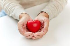 Chiuda su dell'uomo senior con cuore rosso in mani fotografia stock