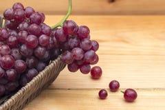 Chiuda su dell'uva rossa in un canestro su un fondo di legno immagine stock libera da diritti