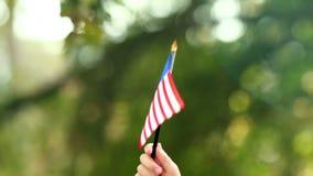 Chiuda su della bandiera americana d'ondeggiamento del ragazzino stock footage