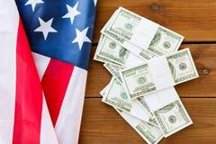 Chiuda su della bandiera americana e del denaro contante del dollaro Immagine Stock