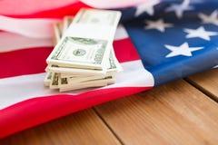 Chiuda su della bandiera americana e del denaro contante del dollaro Fotografie Stock Libere da Diritti