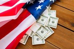 Chiuda su della bandiera americana e del denaro contante del dollaro Fotografia Stock