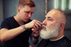 Chiuda su della barba dei clienti della guarnizione del barbiere nel negozio di barbiere immagini stock