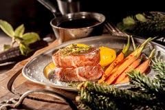 Chiuda su della bistecca di raccordo del verro sul piatto con le verdure fotografie stock