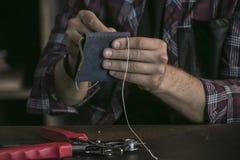 Chiuda su della borsa di cucito del produttore del cuoio della mano dell'uomo di colore blu con il filo Immagine Stock