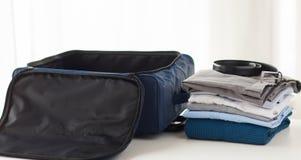 Chiuda su della borsa e dei vestiti di viaggio d'affari Immagini Stock