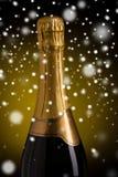 Chiuda su della bottiglia del champagne con l'etichetta dorata Immagine Stock