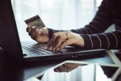 Chiuda su della carta di credito della tenuta della donna della mano e computer portatile usando per il concetto online di acquis fotografia stock libera da diritti