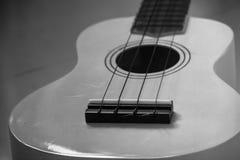 Chiuda su della chitarra delle ukulele dello strumento musicale sulla pavimentazione in piastrelle grigia fotografia stock
