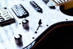 Chiuda su della chitarra elettrica moderna su fondo nero immagini stock