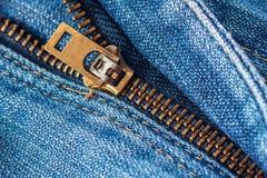 Chiuda su della chiusura lampo in blue jeans Immagine Stock