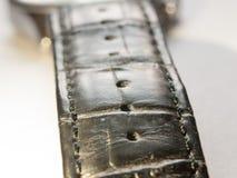 Chiuda su della cinghia di cuoio nera per l'orologio su un fondo bianco fotografia stock libera da diritti