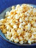 Chiuda su della ciotola ceramica blu riempita di popcorn immagini stock