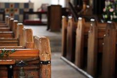 Chiuda su della conclusione di una fila dei banchi di chiesa di legno in uno sto tradizionale Fotografie Stock