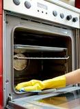 Chiuda su della cucina del forno di pulizia della donna a casa Immagini Stock