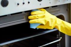 Chiuda su della cucina del forno di pulizia della donna a casa Fotografia Stock