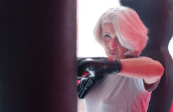 Chiuda su della donna abbastanza senior che punching ball di pugilato Fotografia Stock Libera da Diritti