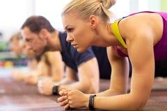 Chiuda su della donna ad addestramento che fa la plancia in palestra Fotografia Stock