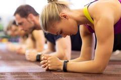 Chiuda su della donna ad addestramento che fa la plancia in palestra Fotografie Stock