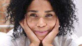 Chiuda su della donna afroamericana sorridente che si trova sullo stomaco a letto video d archivio
