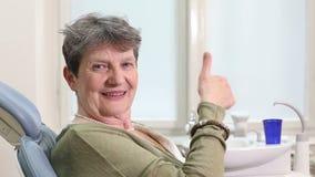 Chiuda su della donna anziana che dà i pollici su alla classificazione dentaria video d archivio