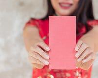 Chiuda su della donna asiatica che porta il vestito tradizionale rosso che tiene la tasca rossa con spazio per i testi fotografia stock libera da diritti