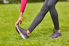 Chiuda su della donna che allunga la gamba all'aperto Fotografia Stock Libera da Diritti